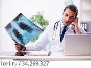 Купить «Young male handsome doctor working in the clinic», фото № 34269327, снято 12 ноября 2019 г. (c) Elnur / Фотобанк Лори