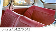 Купить «Red leather seats of an old fashioned compact car. Interior view of an old fashioned compact car with bright red leather seats. The sun shines brightly outside the white car.», фото № 34270643, снято 6 августа 2020 г. (c) easy Fotostock / Фотобанк Лори