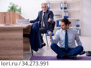 Купить «Two employees doing physical exercises at workplace», фото № 34273991, снято 7 октября 2019 г. (c) Elnur / Фотобанк Лори