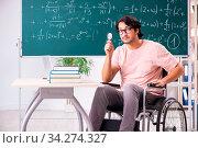 Купить «Young handsome man in wheelchair in front of chalkboard», фото № 34274327, снято 5 августа 2020 г. (c) easy Fotostock / Фотобанк Лори