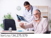 Купить «Young male doctor and old patient in antismoking concept», фото № 34275579, снято 9 сентября 2019 г. (c) Elnur / Фотобанк Лори