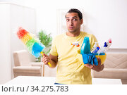 Купить «Young male contractor doing housework at home», фото № 34275783, снято 20 августа 2019 г. (c) Elnur / Фотобанк Лори