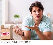 Купить «Man opening fragile parcel ordered from internet», фото № 34276107, снято 4 июля 2018 г. (c) Elnur / Фотобанк Лори