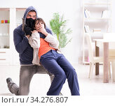 Armed man assaulting young woman at home. Стоковое фото, фотограф Elnur / Фотобанк Лори