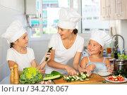 Купить «Little cooks learn with their mom how to cook a salad in the kitchen», фото № 34278067, снято 5 августа 2020 г. (c) Яков Филимонов / Фотобанк Лори