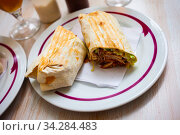 Turkish wrapped dish durum halved on plate. Стоковое фото, фотограф Яков Филимонов / Фотобанк Лори