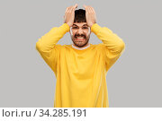angry young man holding to head. Стоковое фото, фотограф Syda Productions / Фотобанк Лори
