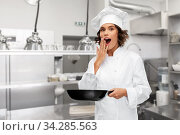 surprised female chef in toque with frying pan. Стоковое фото, фотограф Syda Productions / Фотобанк Лори