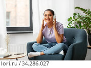 Купить «woman in headphones listening to music at home», фото № 34286027, снято 24 мая 2020 г. (c) Syda Productions / Фотобанк Лори