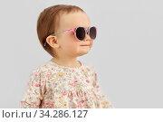 happy little baby girl in sunglasses over grey. Стоковое фото, фотограф Syda Productions / Фотобанк Лори
