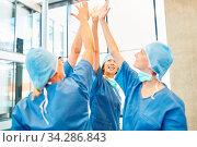 Ärzte im Chirurgie Team geben sich ein High Five für Stärke und Teamgeist. Стоковое фото, фотограф Zoonar.com/Robert Kneschke / age Fotostock / Фотобанк Лори