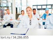 Ärzte in einem Seminar zur Weiterbildung hören aufmerksam ein Referat in der Uni Klinik. Стоковое фото, фотограф Zoonar.com/Robert Kneschke / age Fotostock / Фотобанк Лори