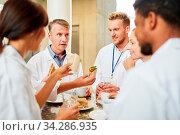 Gruppe Ärzte in der Cafeteria oder Kantine beim Essen und beim entspannten Smalltalk. Стоковое фото, фотограф Zoonar.com/Robert Kneschke / age Fotostock / Фотобанк Лори