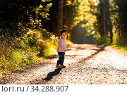 Portrait of 2 years old baby girl in forest walking by herself. Not wanting to follow parents. Concept of child independence. Стоковое фото, фотограф Zoonar.com/Przemyslaw Iciak / easy Fotostock / Фотобанк Лори