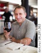 Man sits in restaurant with wineglass. Стоковое фото, фотограф Яков Филимонов / Фотобанк Лори