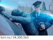 Polizist beim Einbrecher fangen mit Blaulicht und Handschellen. Стоковое фото, фотограф Zoonar.com/Robert Kneschke / age Fotostock / Фотобанк Лори