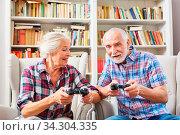 Senioren Paar spielt Videospiel mit Konsole gegeneinander im Wohnzimmer. Стоковое фото, фотограф Zoonar.com/Robert Kneschke / age Fotostock / Фотобанк Лори