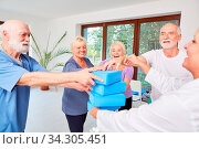 Gruppe Senioren stapelt Yogablöcke als Spiel oder Motivationsübung. Стоковое фото, фотограф Zoonar.com/Robert Kneschke / age Fotostock / Фотобанк Лори