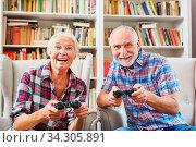 Fröhliches Paar Senioren spielt begeistert Videospiel mit Konsole zuhause. Стоковое фото, фотограф Zoonar.com/Robert Kneschke / age Fotostock / Фотобанк Лори