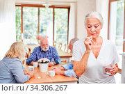 Kranke Seniorin im Altersheim nimmt eine Tablette ein mit einem Glas Wasser. Стоковое фото, фотограф Zoonar.com/Robert Kneschke / age Fotostock / Фотобанк Лори
