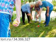 Mann zielt mit der Kugel beim Boccia oder Boule Spiel im Garten mit Freunden. Стоковое фото, фотограф Zoonar.com/Robert Kneschke / age Fotostock / Фотобанк Лори