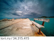 Empty wooden bench on a concrete pier with stormy dramatic clouds accumulating over Alykes Bay in Zante Island, Greece. Стоковое фото, фотограф Zoonar.com/Pawel Opaska / easy Fotostock / Фотобанк Лори