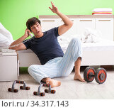 Young man in pajamas doing morning exercises. Стоковое фото, фотограф Elnur / Фотобанк Лори