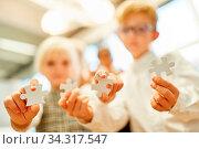 Kinder zeigen verschiedene Puzzleteile als Zeichen für Herausforderung und Geduld. Стоковое фото, фотограф Zoonar.com/Robert Kneschke / age Fotostock / Фотобанк Лори