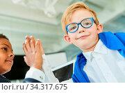 Zwei multikulturelle Kinder geben sich ein High Five Für internationale Kooperation. Стоковое фото, фотограф Zoonar.com/Robert Kneschke / age Fotostock / Фотобанк Лори