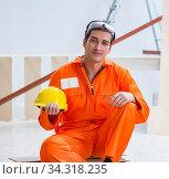 Carpenter wearing yellow hardhat in contractor workshop. Стоковое фото, фотограф Elnur / Фотобанк Лори