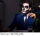 Businessman with scary face mask working late in office. Стоковое фото, фотограф Elnur / Фотобанк Лори