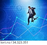 Businessman sliding down on chair in economic crisis concept. Стоковое фото, фотограф Elnur / Фотобанк Лори