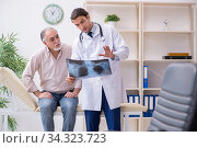 Young male doctor and old patient in antismoking concept. Стоковое фото, фотограф Elnur / Фотобанк Лори