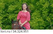 Young woman with braces in pink dress riding a horse. Стоковое видео, видеограф Константин Шишкин / Фотобанк Лори