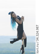 Woman with blue braids on high heels dancing by the pole - leaning on the top of the pole. Стоковое фото, фотограф Константин Шишкин / Фотобанк Лори