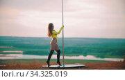 Woman in yellow swimsuit dancing by the pole - rotating next by the pole. Стоковое видео, видеограф Константин Шишкин / Фотобанк Лори