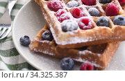 Купить «Belgian waffles on plate with berries», видеоролик № 34325387, снято 8 июля 2020 г. (c) Сергей Петерман / Фотобанк Лори