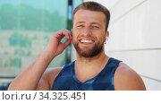 Купить «happy young man with wireless earphones outdoors», видеоролик № 34325451, снято 5 июля 2020 г. (c) Syda Productions / Фотобанк Лори