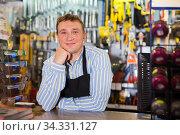 Cheerful seller man in store is trading tools. Стоковое фото, фотограф Яков Филимонов / Фотобанк Лори