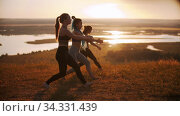 Three young women doing aerobic exercises on sunset - doing lunges. Стоковое видео, видеограф Константин Шишкин / Фотобанк Лори