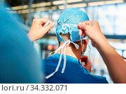Chirurg oder Anästhesist in blauer OP-Kleidung setzt die Haube auf in der Notaufnahme. Стоковое фото, фотограф Zoonar.com/Robert Kneschke / age Fotostock / Фотобанк Лори