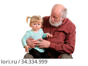 Little granddaughter sitting at lap of her grandpa, isolated. Стоковое фото, фотограф Zoonar.com/Serghei Starus / easy Fotostock / Фотобанк Лори