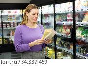Positive woman chooses cheese packaging in supermarket. Стоковое фото, фотограф Яков Филимонов / Фотобанк Лори
