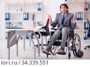 Купить «Young handsome employee in wheelchair working in the office», фото № 34339551, снято 5 августа 2020 г. (c) easy Fotostock / Фотобанк Лори