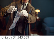 Male detective with tweezers finds sleeve. Стоковое фото, фотограф Tryapitsyn Sergiy / Фотобанк Лори