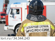 Back view of inscription Emercom of Russia on uniform firefighter of Ministry of Civil Defence, Emergencies and Disaster Relief of Russian Federation MChS (2019 год). Редакционное фото, фотограф А. А. Пирагис / Фотобанк Лори