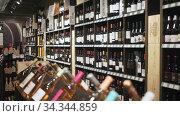 Rack shelves with wine bottles in wine store. Nameplates in Catalan with name of Spanish wine regions. Редакционное видео, видеограф Яков Филимонов / Фотобанк Лори