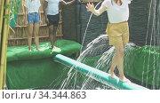 Купить «Young people try to walk the wet log in the theme park», видеоролик № 34344863, снято 5 августа 2020 г. (c) Яков Филимонов / Фотобанк Лори