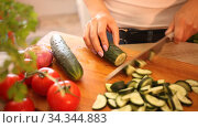 Closeup of slicing fresh cucumber on cutting board. Стоковое видео, видеограф Яков Филимонов / Фотобанк Лори