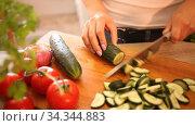 Closeup of slicing fresh cucumber on cutting board. Стоковое видео, видеограф Яков Филимонов / Фотобанк Лори